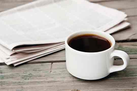 A newspaper and a cup of coffee on a table.