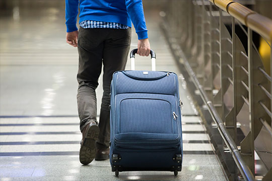 Person traversing an airport walk with luggage.