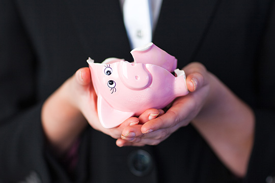 hands holding a broken piggy bank