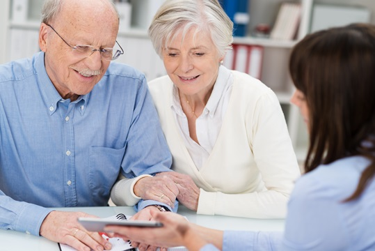 Smiling elderly couple receiving financial advice from a female broker who is showing them a calculator.