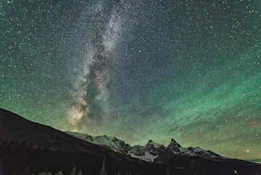 Milky way over the Canadian Rockies with northern light lightening up the night sky in Jasper National Park.