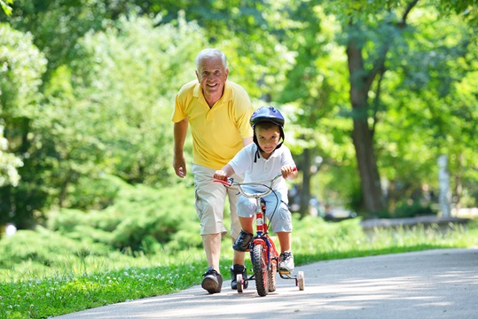 A happy grandfather walking alongside with grand child on a bicycle.