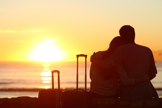 Rear view of a silhouetted couple next to suitcases looking into a sunset.