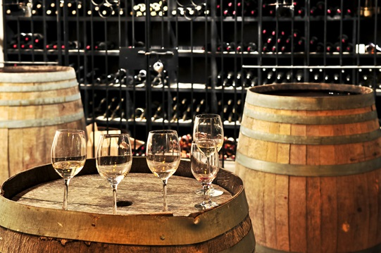 Row of wine glasses on barrel in winery cellar.
