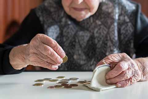 A senior lady counting coins.