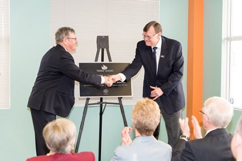 President Jean-Guy Soulière and Bob Edwards shake hands at the unveiling of the building dedication plaque.