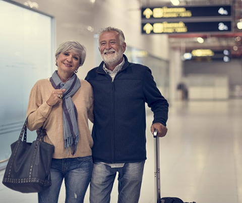 ​​Senior couple walking in an airport.